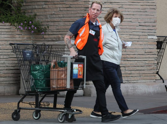 Ralph's grocery store employee helps a customer with her groceries while she wears a mask for the coronavirus in Palm Springs, March 17, 2020.