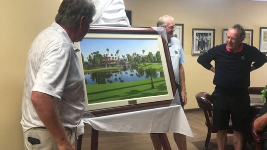 Graeme Baxter, right, looks at his oil painting of the clubhouse at Avondale Golf Club in Palm Desert as it is unveiled by Avondale general Manager Rick Bauer, left, and club member Dave Dunn.