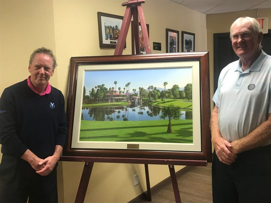 Graeme Baxter, left, shows off his latest golf painting of Avondale Golf Club in Palm Desert with friend and Avondale resident Dave Dunn