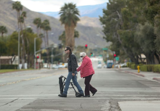 Two people cross a desolate Sunrise Way in Palm Springs as the city has ordered non essential businesses to shut down because of the coronavirus, March 17, 2020.