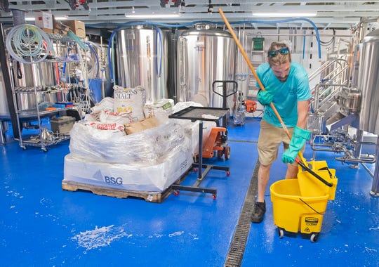 Matt Dyess works on cleaning and sanitizing all the hard surfaces at the Coastal County Brewing Company to help combat the spread of the coronavirus on Tuesday, March 17, 2020.