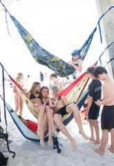 Cole Taliaferro, of West Florida High School, on the bottom hammock, Bianca Hornbrook (West Florida High School), Demery Stacks (West Florida High School), Isaac Dalton (Catholic High School) on the middle hammock, and Will Davis (Bailey Middle School) on the top hammock, hang out under the pier during spring break at Casino Beach in Pensacola on Tuesday, March 17, 2020.