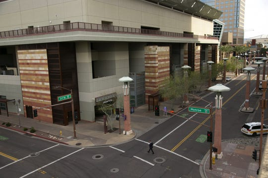 A man crosses Monroe Street near Second Street in front of the Phoenix Convention Center in downtown Phoenix on March 16, 2020.