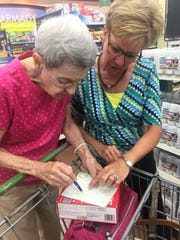 A Duet Volunteer assisting a homebound adult with grocery shopping