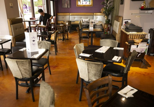 Htoo Gay, a server at Thai Basil, moves chairs around at the empty restaurant along Adams Street in downtown Phoenix on March 16, 2020.