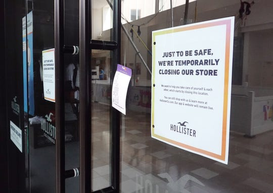 A sign posted at the Hollister clothing store informs shoppers at Chandler Mall that they will be temporarily closed due to the coronavirus.