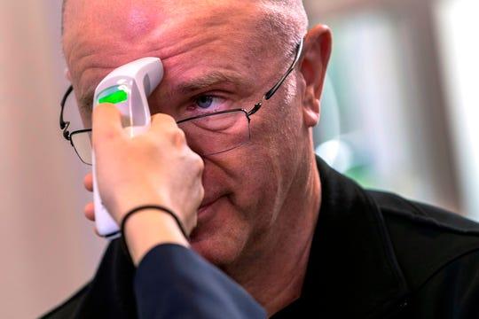 Un reportero tiene su temperatura controlada antes de una sesión informativa realizada por el Grupo de Trabajo Coronavirus en la Sala de Información de Brady Press en la Casa Blanca en Washington, DC, EE. UU., 17 de marzo de 2020.