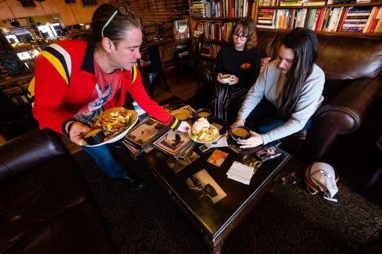 Scott Dambacher, left, serves lunch to Renee Kray, center, and Lizzie Pizzo Monday, March 16, 2020, at The Raven Cafe in Port Huron. Dambacher said he was worried because all of his gigs — he also works for McMorran Place and is a partner for FCK Theatre — were up in the air due to cancelations ordered to help prevent the spread of coronavirus.