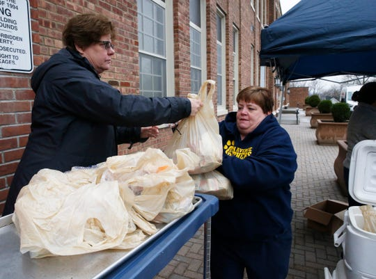 From left, Beacon City School District director of food services Karen Pagano and school cook Margaret Kinney move meals into coolers before distribution to students at South Avenue Elementary School in Beacon on March 17, 2020.