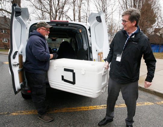 From left, school courier Dennis Lahey and superintendent Matt Landahl unload a cooler of meals to be distributed to students at South Avenue Elementary School in Beacon on March 17, 2020.