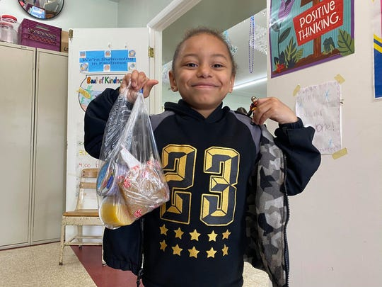 Emmanuel Orrego holds a sack of breakfast provided by the Poughkeepsie City School District at Harriett Tubman Apartments in the City of Poughkeepsie on Tuesday, March 17, 2020.