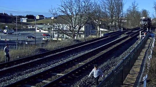 """This image made from a video posted by Virtual Railfan, which describes itself as the """"premier provider of LIVE train cams from some of the busiest spots on earth,"""" shows a group of people running on railroad tracks in Greencastle, Pa., seconds before a southbound train, seen in the upper right, barrels through."""