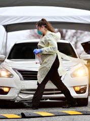 Medical assistant Angelica Young carries a testing kit at the drive up COVID-19 coronavirus testing space at WellSpan Family Medicine - Cape Horn in Windsor Township, Tuesday, March 17, 2020. Candidates must be directed to the facility for testing by a physician prior to arrival. Dawn J. Sagert photo