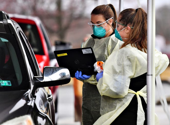 Medical assistants Ashley Moody, left, and Angelica Young prepare to administer swab testing at the drive up COVID-19 coronavirus testing site at WellSpan Family Medicine - Cape Horn in Windsor Township, Tuesday, March 17, 2020. Candidates must be directed to the facility for testing by a physician prior to arrival. Dawn J. Sagert photo