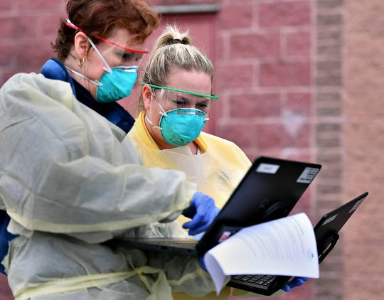 Ann Elliott, R.N., left, and clinical operations coordinator and patient safety officer Jennifer Strayer work together at the drive up COVID-19 coronavirus testing site at WellSpan Family Medicine - Cape Horn in Windsor Township, Tuesday, March 17, 2020. Candidates must be directed to the facility for testing by a physician prior to arrival. Dawn J. Sagert photo