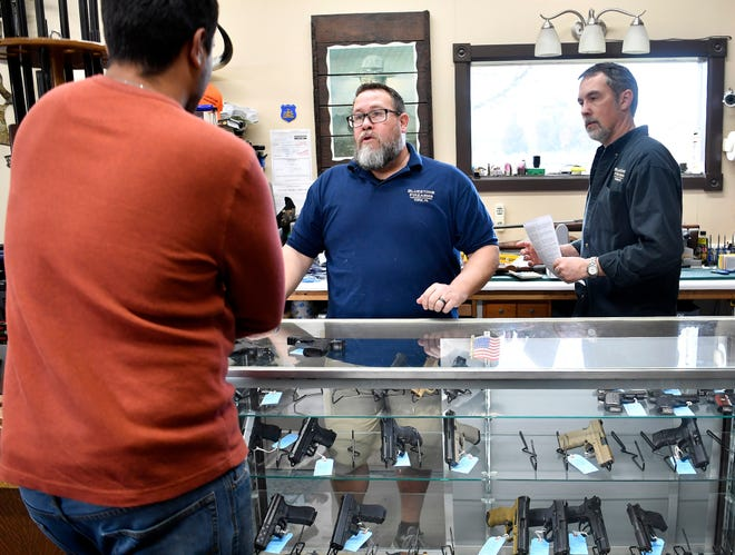 Rick Brubaker, center, and Jeff Rodemyer help a first-time gun buyer with his handgun selection at Bluestone Firearms in Lower Windsor Towship, Tuesday, March 17, 2020. 