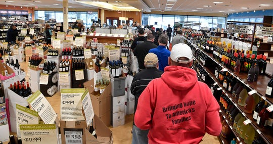Shoppers wait in line to check out at the Wine and Spirits store on Market Street in Springettsbury Township, Tuesday, March 17, 2020. The PALCB stores were slated to close at 9 p.m. Tuesday as part of the effort to control the spread of COVID-19. John A. Pavoncello photo