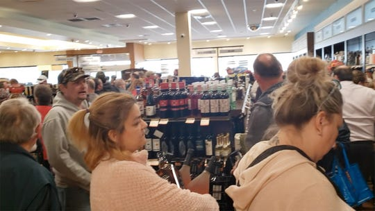 A very long line snakes around the state-owned liquor store in West Manchester Township late Monday after word that the stores would close around the state to slow the spread of the coronavirus.