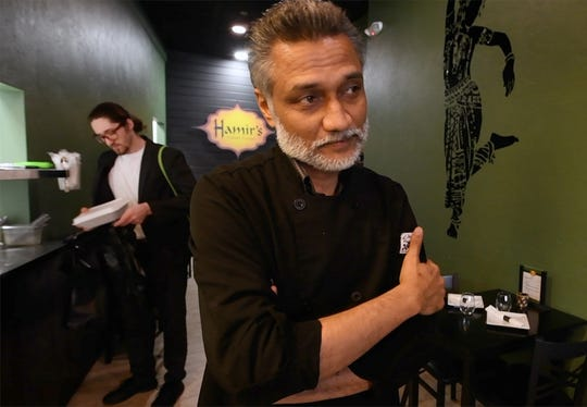 Hamir's Indian Fusion owner/chef Hamir Patel talks about the restaurant closures while a runner prepares take-out in the background. The York restaurant on South George Street will be offering takeout during the coronavirus closure.