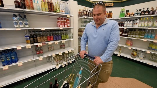 "Dave Bode stocks up at the state-owned liquor store in Manchester Township surrounded by dwindling stock, joking, ""If we run out of food, at least we have liquor."""