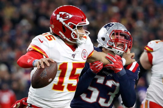 Chiefs quarterback Patrick Mahomes (15) tries to fend off  New England middle linebacker Kyle Van Noy during a game last season.