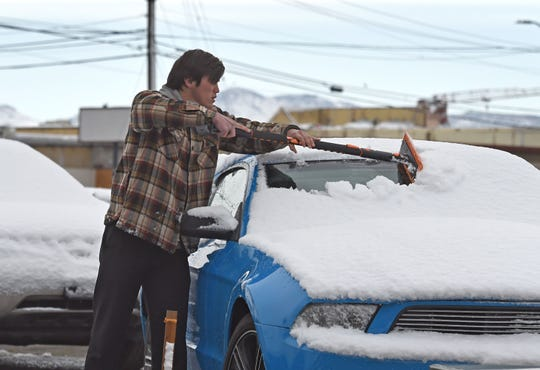 Skylor Starr Wong clears the snow off cars in the used car lot on Virginia Street Tuesday morning. More snow is expected on Wednesday.
