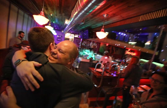 Dave Chappus, co-owner, second from left facing camera, hugs customers as they leave just before 8 pm as Roar closes its doors  Monday, March 16, 2020.  New York state announced that they will limit all bars and restaurants to takeout and delivery services only starting tonight.
