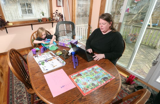 Beth Rhodes works at her laptop from her kitchen table with her four-year-old daughter Annie, who is home from her pre-kindergarten classes because of the coronavirus shutdown.