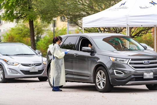 A medical professional wearing protective clothing administers a test to patient at a drive-through COVID-19 testing facility at Baylor Scott & White Medical Center in Round Rock.