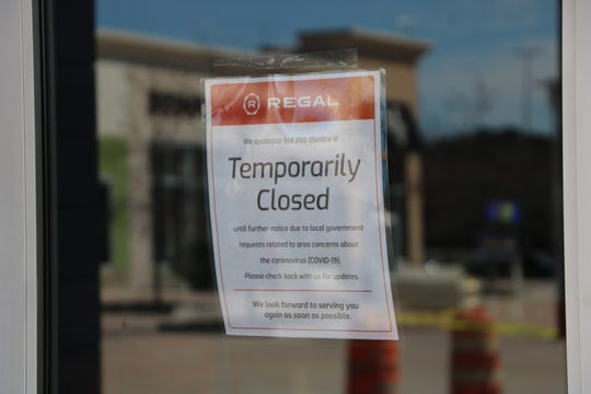 Signs on the doors of the Regal Cinema in Salisbury March 17, 2020, inform customers of the company's decision to close all of its cinemas nationwide until further notice due to the coronavirus outbreak. Movies that would have been playing this week include Onward, Emma and Birds of Prey.