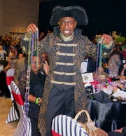 McDonald's Guru Roy Griggs stands by his table and holds up beads at Krewe Harambee Grand Bal.