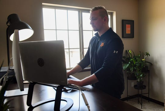 Travis Adney works in his home office on Tuesday, March 17, in Sioux Falls. Adney, a senior digital strategist at local advertising firm Lawrence and Schiller, is working remotely due to coronavirus concerns.
