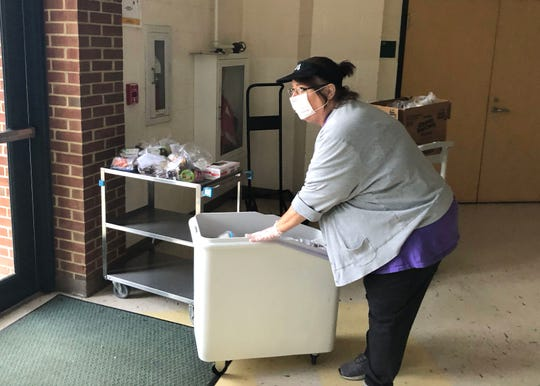 Dee Abshire helps set up a meal pick-up station at Westwood Hills Elementary School Tuesday morning, March 17. Meals are available to families of children in the Waynesboro Public School system during the current school closure.