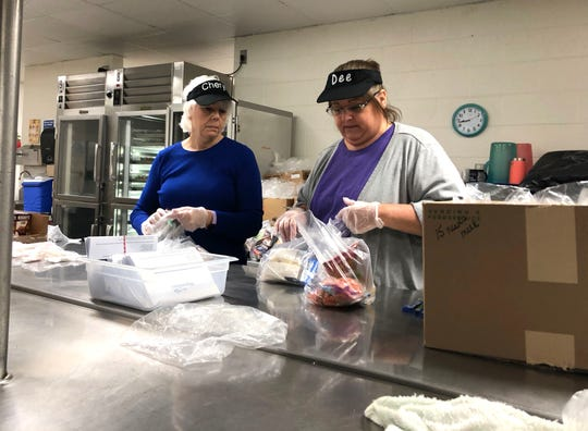 Cheryl Adkins and Dee Abshire work to prepare meals Tuesday morning, March 17, for Waynesboro Public School families to pick up at Westwood Hill Elementary School.