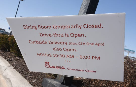 A sign is posted by the Chick-fil-A drive-thru detailing new guidelines Tuesday, March 17, 2020, in Waite Park.