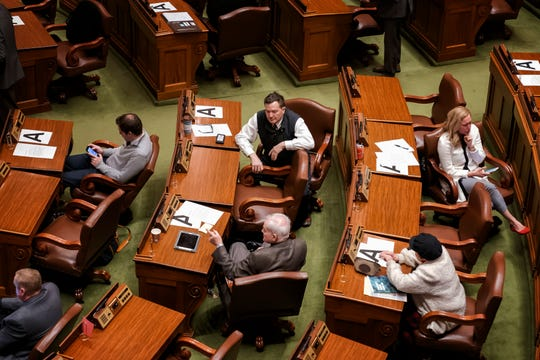 Desks and chairs where Minnesota state legislators are allowed to sit are marked with a letter A in order to keep them six feet away from each other amid concerns about the new coronavirus, forcing some to sit in the visitors gallery and in the alcoves at the back of the chamber, Monday, March 16, 2020, in St. Paul, Minn. They were all asked Monday to be on call within an hour's notice. (Glen Stubbe/Star Tribune via AP)