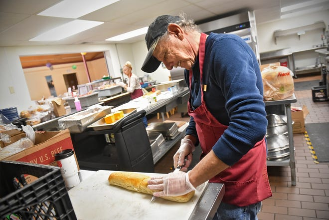 Bruce Lenzen slices bread for sandwiches Tuesday, March 17, 2020, at the Salvation Army shelter in St. Cloud. Due to COVID-19 concerns, meals won't be served in the shelter's dining room. Sack lunches will be provided.