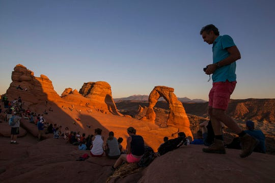 FILE - In this Sept. 8, 2016, file photo, people gather to watch the sunset at Delicate Arch in Arches National Park near Moab, Utah. Most of America's national parks remain open as some of the last refuges for weary Americans sick of being stuck at home, but many are closing visitor centers, shuttles, lodges and restaurants in hopes of containing the spread of the coronavirus. (Spenser Heaps/The Deseret News via AP, File)