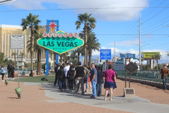 People stand in line waiting to take a picture by the iconic Welcome to Las Vegas sign on St. Patrick's Day 2020. The city is clearing out as hotels and casinos shut down due to the coronavirus.