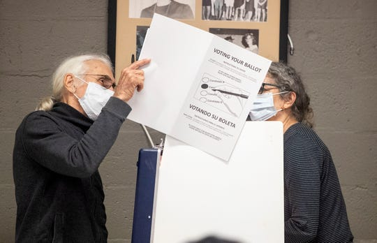 Jim Roche, left, and Alexa Kleinbard wear masks while voting during the Florida primary election, Tuesday, March 17, 2020. Both are over 65 and felt it was important to exercise their right to vote while being cautious about the coronavirus.