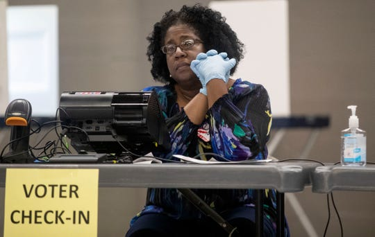 Poll workers wear gloves and have bottles of hand sanitizer ready for voters as they cast their ballot in the Florida primary election, Tuesday, March 17, 2020.