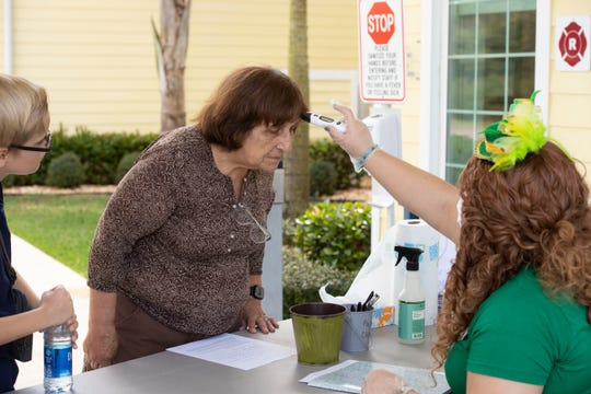 """To prevent the spread of the coronavirus, Meals on Wheels volunteers Luke Parsons, 12, of Palm Beach Gardens, and Analucia Vieira, of Stuart, are screened with a questionnaire and a temperature check by Kane Center activities assistant Olivia Moore before proceeding to their food delivery routes Tuesday, March 17, 2020, at the Kane Center in Martin County. Vieira, who typically volunteers two days a week, is now assisting four days a week as the number of volunteers declines. """"If not for us, who will deliver food? They need us,"""" Vieira said. """"We want to help. It's very important."""""""