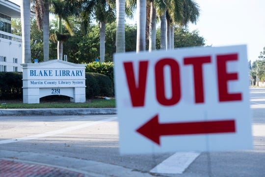 A vote sign points toward the entrance of Martin County Precinct  5 on presidential primary voting day Tuesday, March 17, 2020, at the Blake Library in Stuart.