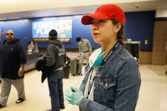 Jessica Arzavala talks about how her professor gave her a surgical mask and gloves for her flight back home to El Paso while grabbing her luggage at the El Paso International Airport Tuesday, March 17. People rearranged their flights or booked them last minute in order to make it back to El Paso as soon as possible in response to coronavirus spreading throughout the country.