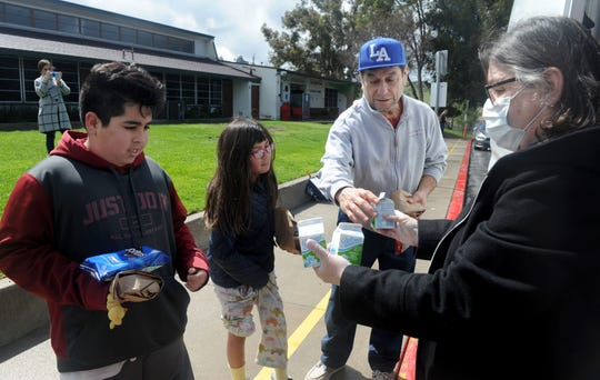 Left to right, Joshua Munoz and Valentina Valencia pick up lunches with Joshua's grandfather Miguel Valencia from Susan Robinson, cafeteria manager for Conejo Valley Unified School District at Conejo Elementary on Tuesday.