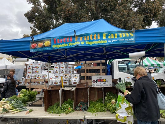 A shopper visits the Tutti Frutti Farms booth at the Saturday farmers market in downtown Ventura. Farmers markets throughout Ventura County continue to take place with precautionary measures to help fight the spread of the coronavirus.