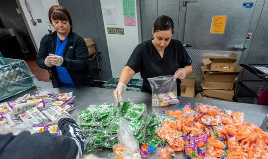"""Violet Chavez, center, and other cafeteria workers at Visalia Unified's Food Production Center prepare """"grab-n-go"""" meals on Tuesday, March 17, 2020 for students during the school shut down."""