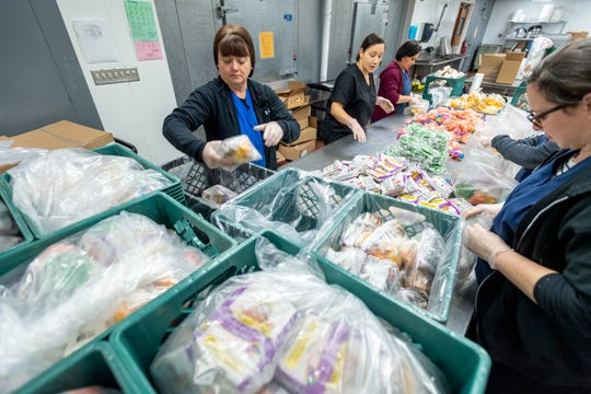 """Sara Brumley, left, and other cafeteria workers at Visalia Unified's Food Production Center prepare """"grab-n-go"""" meals on Tuesday, March 17, 2020 for students during the school shut down."""