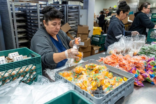 """Delia Scott, left, and other cafeteria workers at Visalia Unified's Food Production Center prepare """"grab-n-go"""" meals on Tuesday, March 17, 2020 for students during the school shut down."""