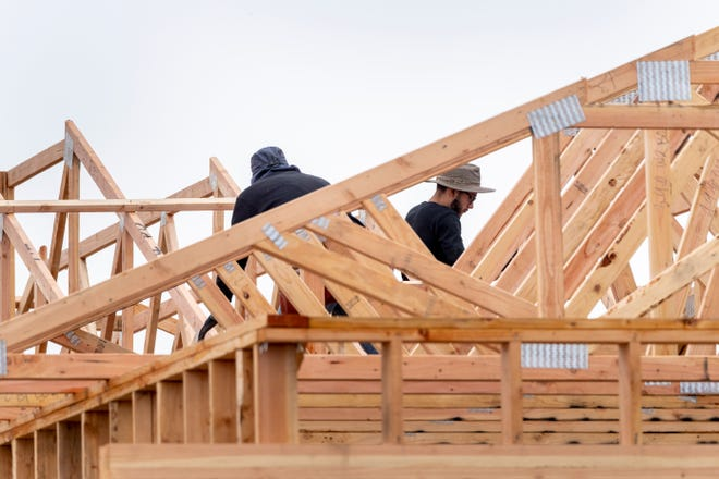 Construction workers continue framing a house in the Los Pines subdivision on Monday, March 16, 2020.